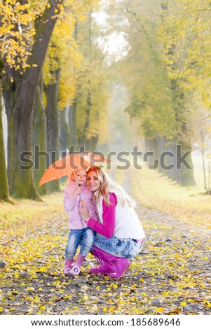 mother and her daughter with umbrella in autumnal alley - stock photo