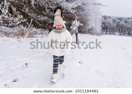 Mother and her daughters have fun near the snow-covered forest on a winter day. They ride a sled and play with snow. Winter fun mood