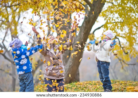 mother and her daughters in autumn park - stock photo