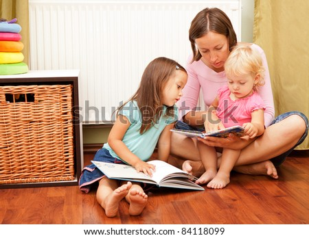 mother and her daughters reading a book on the floor - stock photo