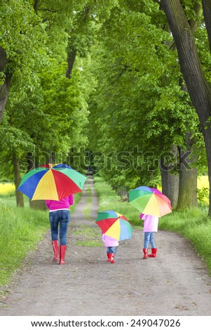 mother and her daughters with umbrellas in spring alley - stock photo