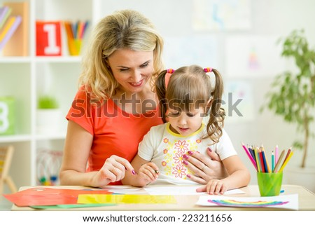 mother and her kid drawing with pencils together - stock photo