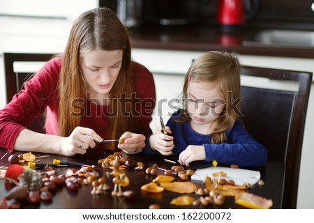 Mother and her kid making chestnuts creatures together - stock photo