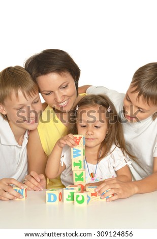 Mother and her kids playing with cubes isolated on white - stock photo