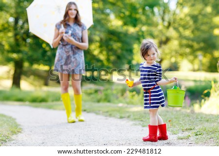 Mother and her little adorable kid girl in rain boots, playing together in summer sunny park, on warm day. - stock photo