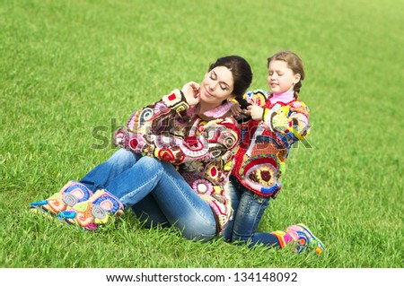 Mother and her little daughter at the meadow - stock photo