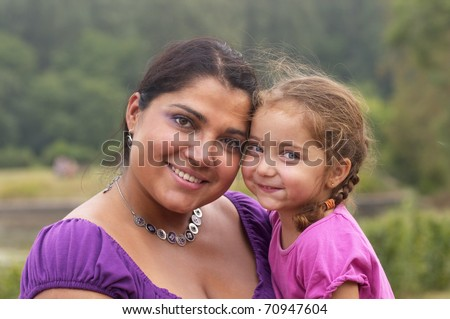 Mother and her little daughter in the city garden - stock photo