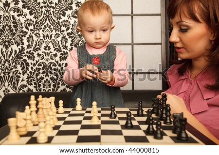 Mother and her little daughter near chess board. Horizontal format. Indoor. - stock photo