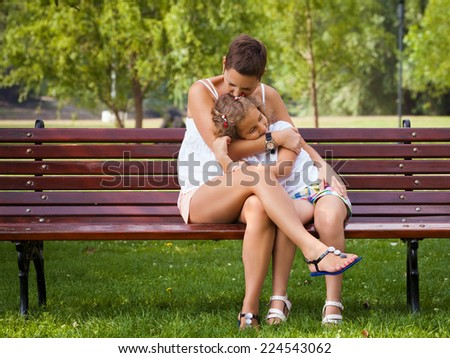 Mother and her little daughter sitting on the bench in a park - stock photo