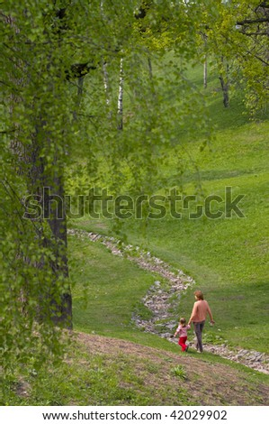 Mother and her little daughter walking in the summer park