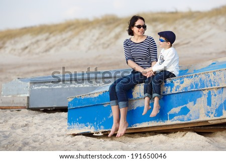 Mother and her little son sitting on a boat - stock photo