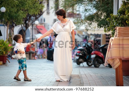 Mother and her little son walking in city - stock photo