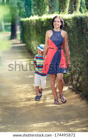 Mother and her little son walking in city park - stock photo