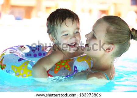 Mother and her little son with floating ring swimming in rough water of the pool.  Family fun in waterpark. - stock photo