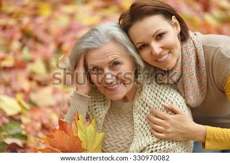 Mother and her nice daughter in autumn park - stock photo