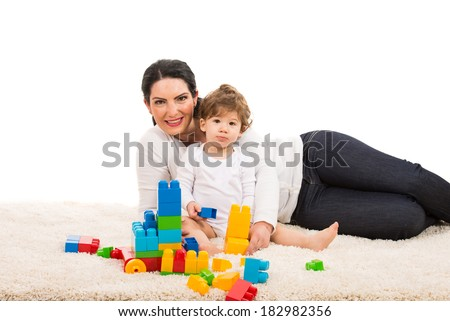 Mother and her son boy sitting on fur carpet and playing with building bricks isolated on white background - stock photo