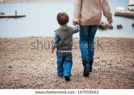 Mother and her son by the sea - stock photo