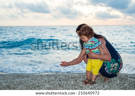 Mother and her son collect little pebbles on the beach - stock photo