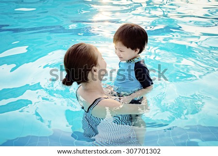 Mother and her son having fun in the swimming pool at sunset : Soft Focus - stock photo