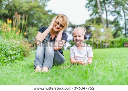Mother and her son having fun with headphones and music