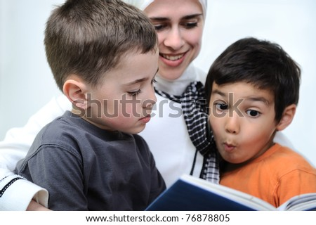 Mother and her son in the nature, reading together - stock photo
