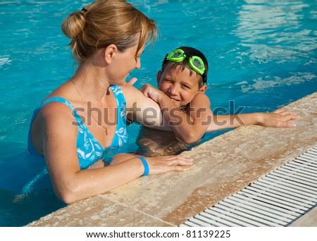 Mother and her son in the swimming pool. Swimming lessons. - stock photo