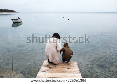 Mother and her son looking for a fish  - stock photo