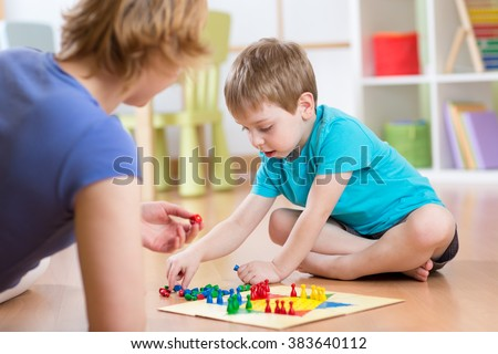 Mother and her son playing in board game - stock photo