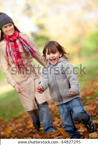 Mother and her son running at the park in autumn - family concepts - stock photo