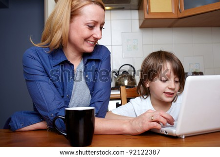 Mother and her son sits at kitchen table and play with small laptop - stock photo