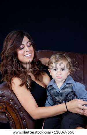 Mother and her son sitting on a couch in an affectionate embrace with eye contact and smiles