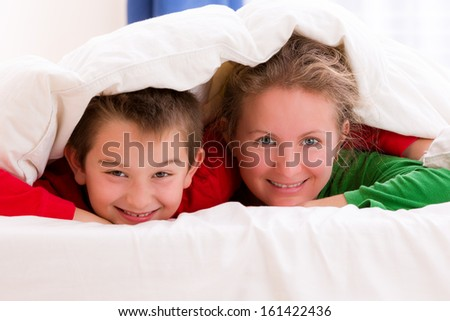 Mother and her son under the blanket with Christmas color pajamas, smiling to you cheerfully - stock photo