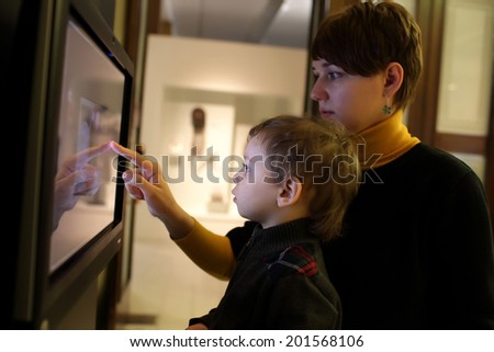 Mother and her son using touch screen in a museum - stock photo