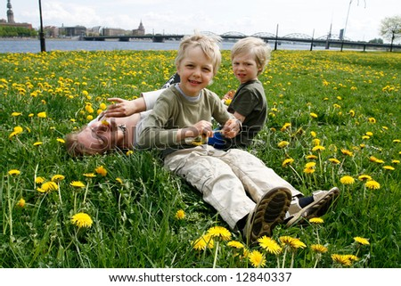 Mother and her sons in meadow with dandelions. Riga city in foreground. - stock photo