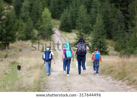 Mother and her three children and dog hiking in forest in an autumn day. They are walking on a way and wearing backpacks. Back view - stock photo