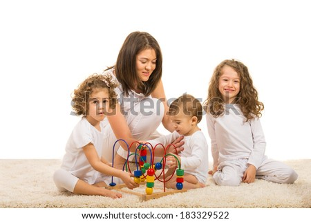Mother and her three kids playing with wooden toy home - stock photo