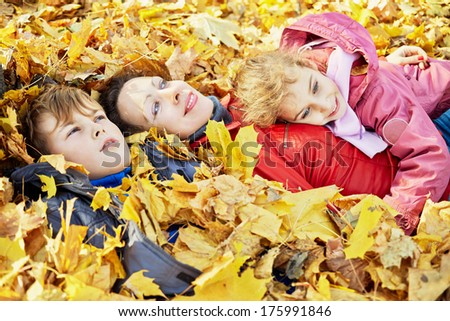 Mother and her two children lie in autumn park in drift of fallen leaves and look at the sky - stock photo
