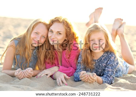 mother and her two daughters on the beach in summer - stock photo