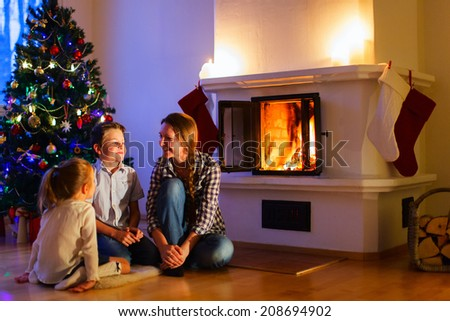 Mother and her two little kids sitting by a fireplace in their cozy family home enjoying winter evening - stock photo