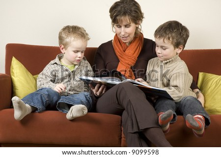 Mother and her two sons reading a book on a couch.