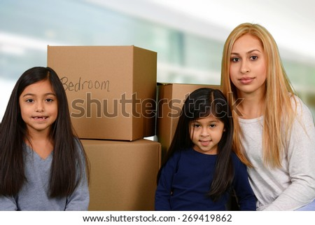 Mother and her two young daughters packed moving boxes - stock photo