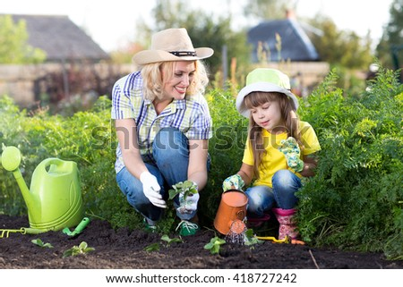 Mother and kid daughter planting strawberry seedling in a garden. Little girl watering new plants. - stock photo