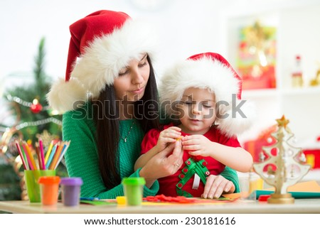 mother and kid in Santa hats making christmas tree of plasticine