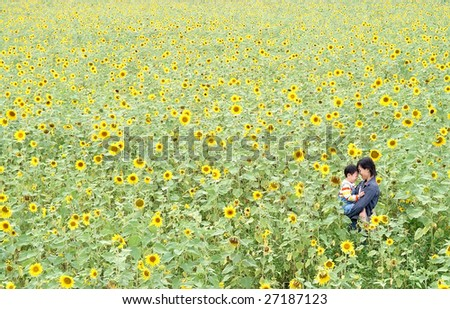 mother and kid in sunflower field - stock photo