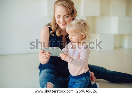 mother and kid play at tablet computer at nursery - stock photo