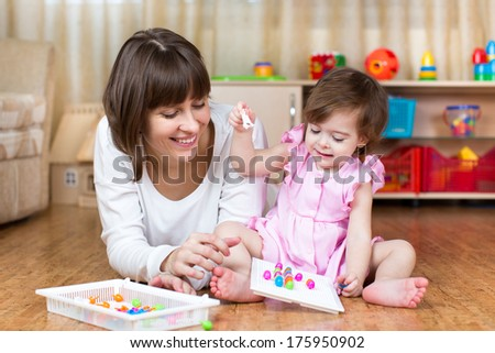 mother and kid play together in home interior - stock photo