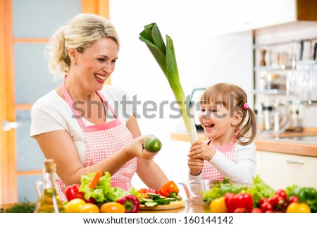 mother and kid preparing healthy food and having fun - stock photo