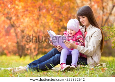 mother and kid reading a book outdoors in autumn - stock photo