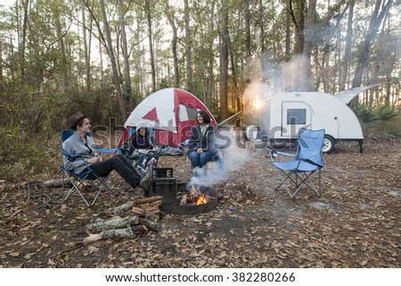 Mother and kids camping with tent and teardrop trailer - stock photo