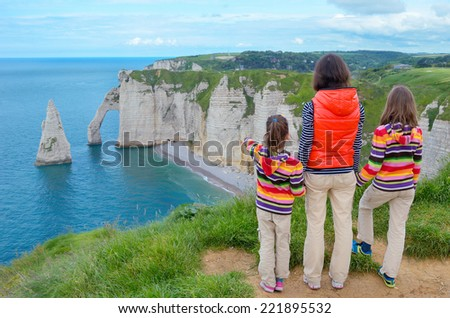 Mother and kids looking at beautiful sea view, family hiking on vacation in France, Etretat  - stock photo